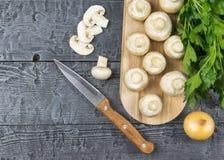 Champiñones frescos con perejil y la cebolla en tabla de cortar en la tabla rústica La comida vegetariana está en la tabla La vis Imagen de archivo