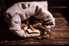 Champi?ones secados en un bolso de lino en fondo marr?n del vintage imagenes de archivo