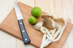 Champignon d'huître du Thibet sur la planche à découper en bois avec le couteau et le lem Photo libre de droits