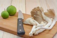 Champignon d'huître du Thibet sur la planche à découper en bois avec le couteau et le lem Photos stock