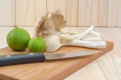Champignon d'huître du Thibet sur la planche à découper en bois avec le couteau et le lem Image stock