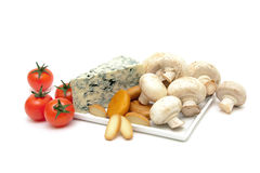 Champignon mushrooms, cherry tomatoes and cheese close-up on a w Royalty Free Stock Photos