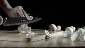 Champignon mushrooms, cut with a knife on a wooden stock video