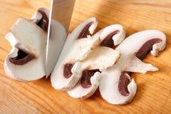 Champignon mushrooms. Cutting champignon mushroom on wooden cutting board Royalty Free Stock Photography