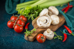 Champignon mushrooms. Fresh mushrooms champignons on a wooden cutting board, parsley greens, celery stalks, cherry tomatoes and hot red chili pepper on a dark Royalty Free Stock Image