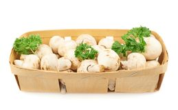 Champignon mushrooms and greens. In a wooden box isolated over the white background Royalty Free Stock Images
