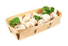 Champignon mushrooms and greens. In a wooden box isolated over the white background Royalty Free Stock Photos