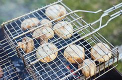 Champignon mushrooms on grill in summer Stock Photos