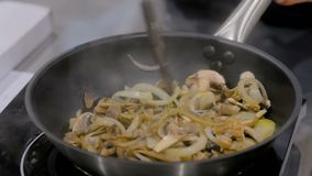 Champignon mushrooms and onions frying and sizzling in pan. Chef hand stirring sliced champignon mushrooms and onions with spatula in frying pan with oil stock video