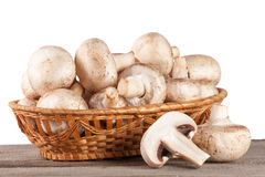 Champignon mushrooms in a wicker basket on a wooden table with white background.  Royalty Free Stock Images
