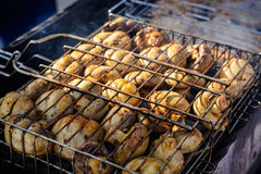 Champignon white mushrooms grilled on grill or barbecue in smoke coals Stock Image