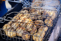Champignon white mushrooms grilled on grill or barbecue in smoke coals Royalty Free Stock Images