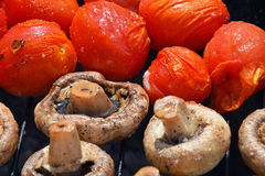 Champignon white mushrooms and tomatoes on grill Royalty Free Stock Photo