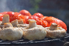 Champignon white mushrooms and tomatoes on grill Royalty Free Stock Images