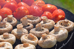 Champignon white mushrooms and tomatoes on grill Royalty Free Stock Image
