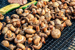 Champignon witte die paddestoelen op grill of BBQ stoom worden geroosterd en kleine dalingen van water Kokende paddestoelen op de Royalty-vrije Stock Afbeelding