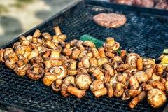 Champignon witte die paddestoelen op grill of BBQ stoom worden geroosterd en kleine dalingen van water Kokende paddestoelen op de Stock Foto