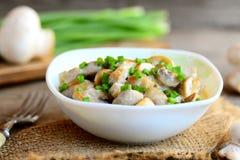 Champignons à une sauce à crème sure Les champignons cuisent avec la crème sure et les oignons verts frais dans une cuvette Recet Photos libres de droits