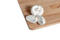 Champignons σε έναν ξύλινο πίνακα, άσπρο υπόβαθρο Στοκ Φωτογραφία
