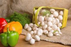 Champignons в корзине, вместе с овощами на таблице Стоковые Изображения