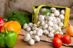 Champignons в корзине, вместе с овощами на таблице Стоковое Изображение