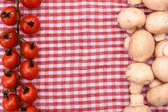 Champignons грибов белизны и красные томаты вишни лежат на красном полотенце, месте для текста, предпосылки Стоковая Фотография RF