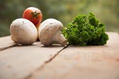 Champignons avec des légumes sur un fond en bois photographie stock libre de droits