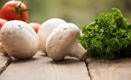 Champignons avec des légumes sur un fond en bois image stock