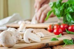 Champignons blancs coupés en tranches sur une planche à découper avec le basilic Image stock