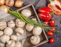Champignons in a box and vegetables on a table. Champignons in a wooden box, onion, red pepper, cherry and napkin on a dark wooden surface Royalty Free Stock Images