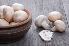 Champignons in a ceramic plate on old wood Stock Images