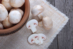 Champignons in a ceramic plate on old wood table Stock Photos