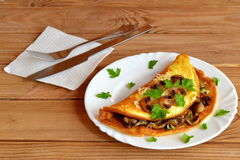 Champignons, cheese and herb omelet recipe. Spoon mushroom and cheese mix over one half of the scrambled eggs Royalty Free Stock Photo