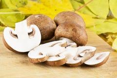 Champignons coupés en tranches de champignon de paris sur une table en bois photo stock