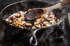 Champignons coupés en tranches faisants sauter dans une poêle photos stock