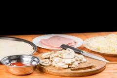 Champignons coupés en tranches sur le conseil en bois rond avec du jambon et le fromage coupés en tranches à l'arrière-plan Image libre de droits
