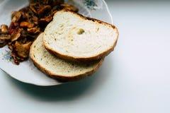 Champignons cuits et deux morceaux de pain photographie stock