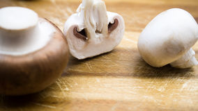 Champignons on a cutting board. Champignons on a wooden cutting board Royalty Free Stock Images