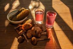 Champignons d'automne et un verre d'eau-de-vie fine Photographie stock libre de droits