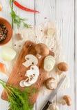 Champignons de champignon de paris de Brown sur une planche à découper Herbes et oignons en bois blancs de bureau Photographie stock