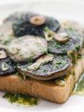 Champignons de couche de gisement d'ail sur le pain grillé Photos stock