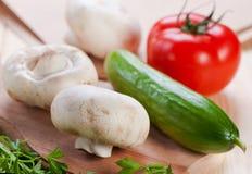Champignons de couche et légumes à bord. Image stock