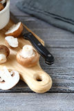 Champignons de couche frais sur une planche à découper Photographie stock libre de droits