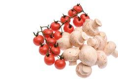 Champignons de paris de champignons et tomates-cerises rouges d'isolement sur le fond blanc Photographie stock libre de droits