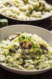 Champignons et parmesan italiens de courgette de risotto dans le plat blanc image stock