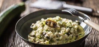 Champignons et parmesan italiens de courgette de risotto dans le plat foncé image stock