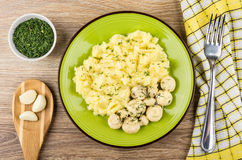 Champignons with mashed potatoes, greens, garlic on spoon, fork. Marinated champignons with mashed potatoes in plate, greens, garlic on spoon, fork on wooden Stock Photography