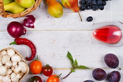 Champignons, raisin, prunes, oignon, tomates, poivrons de piments, verre de vin rouge, pommes et poires dans le panier Vue de ci- image stock