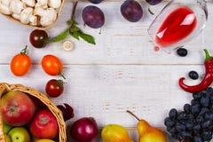 Champignons, raisin, prunes, oignon, tomates, poivrons de piments, verre de vin rouge, pommes et poires dans le panier Vue de ci- photographie stock libre de droits