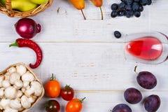 Champignons, raisin, prunes, oignon, tomates, poivrons de piments, verre de vin rouge, pommes et poires dans le panier Vue de ci- photo libre de droits
